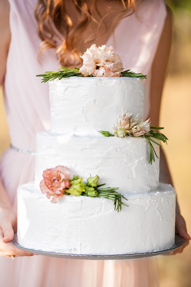 Bride Holding A Wedding Cake Decorated With Pink Flowers